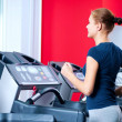 Young woman at the gym run on on a machine - Stockfoto