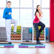 Man and woman at the gym doing stretching - Stock Photo