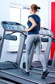 Jonge vrouw op de sportschool op draaien op een machine — Stockfoto