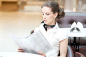Serious business woman reading newspaper — Stock Photo