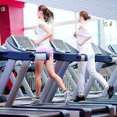 Dos jóvenes mujeres deportivas en máquina — Foto de Stock