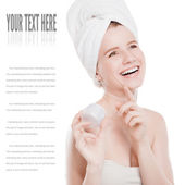 Woman applying moisturizer cream on face — Stock Photo