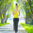Runner - woman running outdoors in green park — Stockfoto