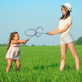 The young girls plays with a racket in badminton — Stock Photo