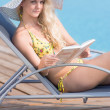 Young woman in swimsuit laying on chaise-longue poolside — Stock Photo #32885973