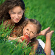 Happy girls on green grass with apple — Foto Stock