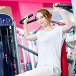 Woman doing splits on machine with weights — ストック写真
