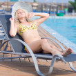 Young woman in swimsuit laying on chaise-longue poolside — Foto de Stock