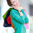 Shopping woman with phone and color bags — Stok fotoğraf