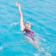 Stock Photo: Woman in goggles swimming back crawl style