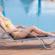 Young woman in swimsuit laying on chaise-longue poolside — Stock Photo #32887209