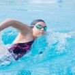 Woman in goggles swimming front crawl style — Stock Photo