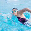Woman in goggles swimming front crawl style — Stockfoto