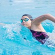 Woman in goggles swimming front crawl style — Stok fotoğraf