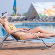 Young woman in swimsuit laying on chaise-longue poolside — Stock Photo #32888163