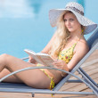 Young woman in swimsuit laying on chaise-longue poolside — Stock Photo #32888197