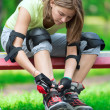 Girl going rollerblading sitting in bench putting on inline skat — Stock Photo