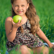 Happy girls on green grass with apple — Stock Photo