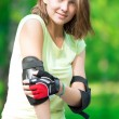 Girl going rollerblading sitting in bench putting on elbow guard — Stock Photo