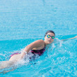 Stock Photo: Woman in goggles swimming front crawl style