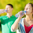 Man and woman drinking from bottle — Stock Photo #32889233