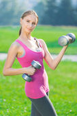 Woman exercising with dumbbell at city park — Foto Stock