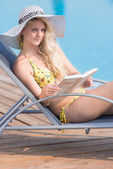 Young woman in swimsuit laying on chaise-longue poolside — Stock Photo