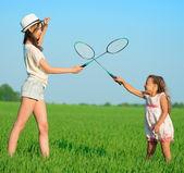 As meninas joga com uma raquete de badminton — Fotografia Stock