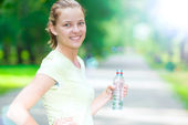 Woman drinking cold mineral water from a bottle after fitness ex — Stock Photo