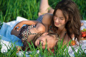 Happy girls on green grass embrace — Stock Photo
