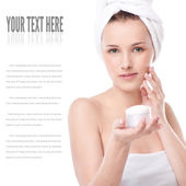 Woman applying moisturizer cream on face — Stock Photo