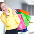 Shopping woman with phone and color bags — Stock Photo