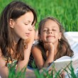 Happy girls reading book on green grass — Stock Photo