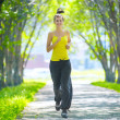 Woman running in green park — Stock Photo