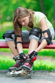 Girl going rollerblading sitting in bench — Stock Photo