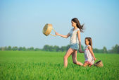 Young happy girls running witch baskets at green wheat field — Foto Stock