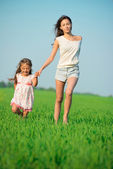 Girls running down green wheat field — Stock Photo