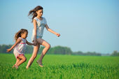 Girls running down green wheat field — Stockfoto