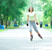 Roller skating sporty girl in park — Stock Photo