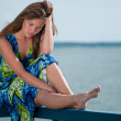 Sad woman sitting over sea at summer day — Stock Photo #8534990