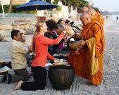 HUA HIN, THAILAND - DEC 28:Victoria Azarenka of Belarus gives food to a monks. Before tennis Match Hua hin World Tennis Invitation at Intercontinental resort on December 28, 2012 in Hua hin, Thailan — Stock Photo