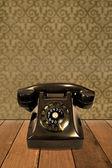 Retro telephone on vintage wallpaper — Stock Photo