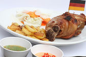 German BBQ pork knuckle served with french fries and salad. — Stock Photo