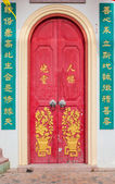 Old red chinese temple door with crave leaf — Stock Photo