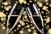 Champagne glasses on bokeh background — Stock Photo