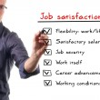 Man writing job satisfaction list on whiteboard - Stockfoto