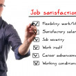 Man writing job satisfaction list on whiteboard — 图库照片