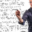 Mwrites mathematical equations on whiteboard — Stock Photo #13956036