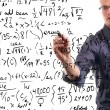 Man writes mathematical equations on whiteboard — Stock Photo