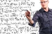 Mann schreibt mathematische gleichungen auf whiteboard — Stockfoto